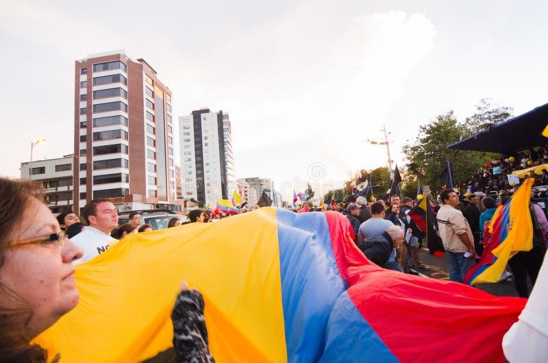 基多,厄瓜多尔- 2016年4月7日:显示一面非常大厄瓜多尔旗子、抗议标志和新闻工作者的人 免版税库存图片
