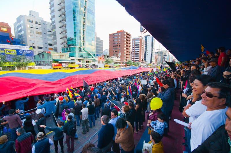 基多,厄瓜多尔- 2016年4月7日:显示一面非常大厄瓜多尔旗子、抗议标志和新闻工作者的人 库存照片