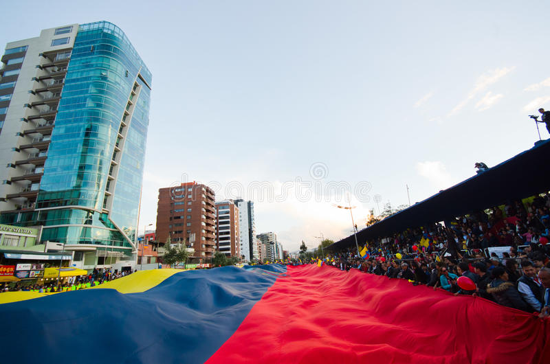 基多,厄瓜多尔- 2016年4月7日:显示一面非常大厄瓜多尔旗子、抗议标志和新闻工作者的人 图库摄影