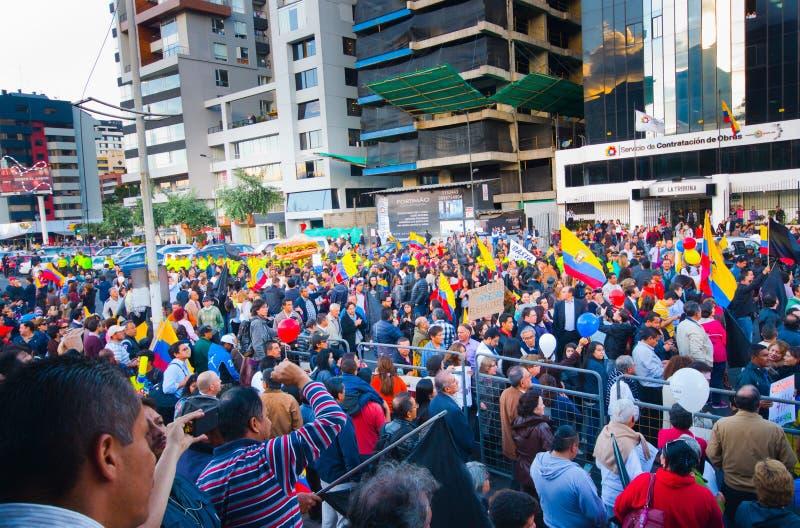 基多,厄瓜多尔- 2016年4月7日:显示一面非常大厄瓜多尔旗子、抗议标志和新闻工作者的人 库存图片