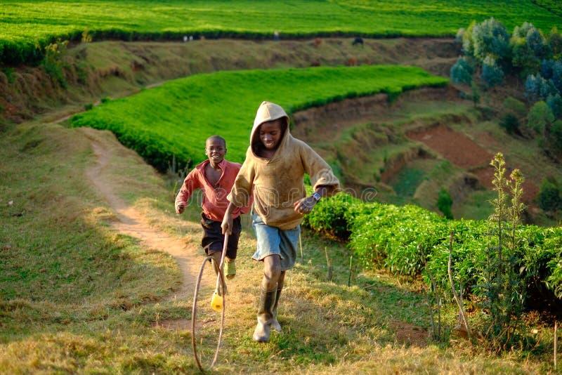 基布耶/卢旺达- 08/25/2016:演奏箍的非洲男孩滚动  库存照片