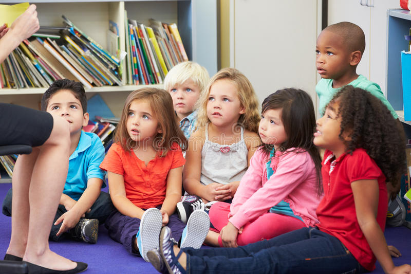 基本的学生在运作与老师的教室 免版税库存照片