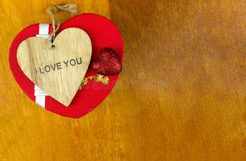 基本的邀请木心脏雕刻了与词组我爱你和有拷贝空间的一个欢乐箱子在土气背景,设计费斯特 免版税库存照片