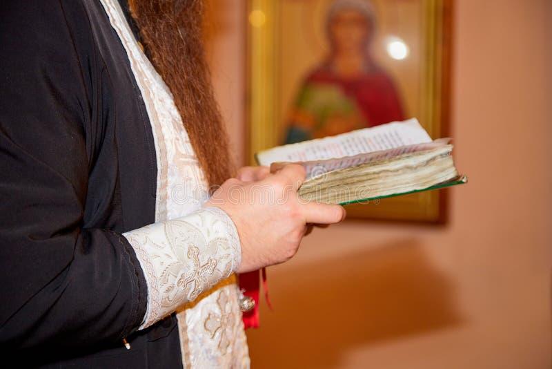 基洛夫,俄罗斯- 2018年10月30日:一位教士的手黑色衣服的有书的 库存图片