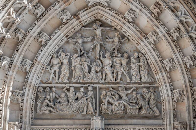 基督场面在十字架上钉死在圣徒维塔斯大教堂主要入口门户的在布拉格,捷克,细节,特写镜头 免版税库存图片