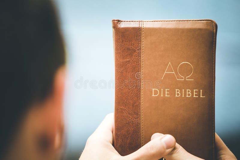 基督徒传教者:年轻人拿着圣经,祈祷 免版税库存图片