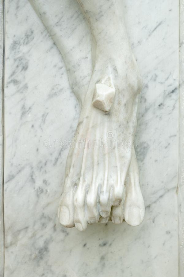基督的脚钉牢了对十字架 库存照片