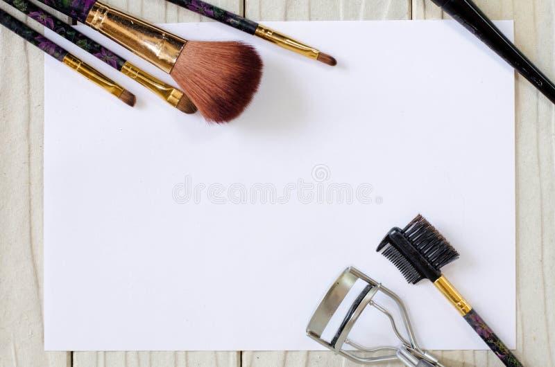 基础和刷子在白色木头和纸背景 库存图片