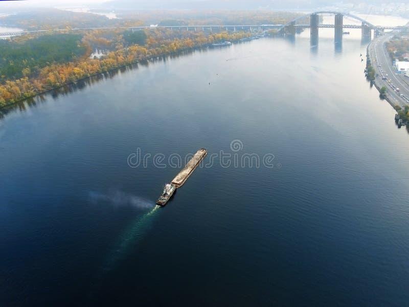 基辅和河在日落的Dnipro风景空中都市风景  有沙子朝向在河下的粒状材料的拖轮支持的驳船 免版税库存照片
