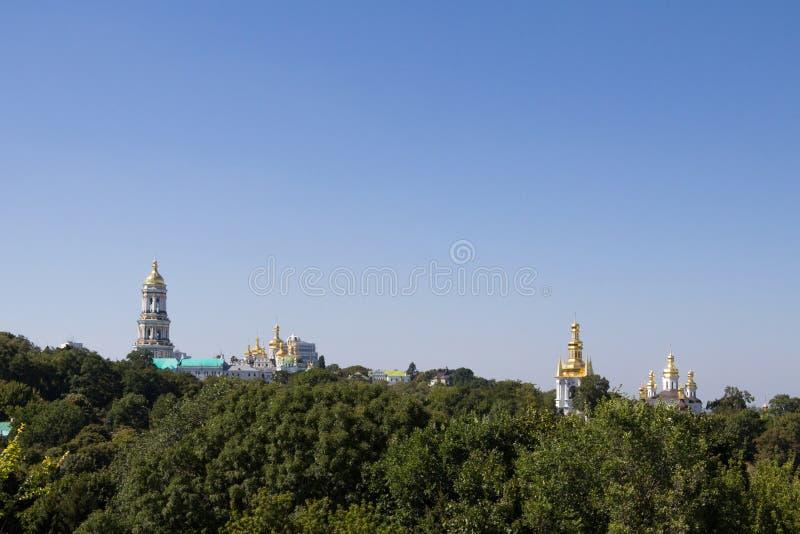 基辅小山全景与地平线的被做Pechersk拉夫拉修道院和教会圆顶,围拢由木头 免版税库存图片