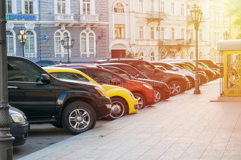 基辅,乌克兰–2018年5月09日:在城市街道上的停放的汽车有阳光的 停车处在老镇 图库摄影