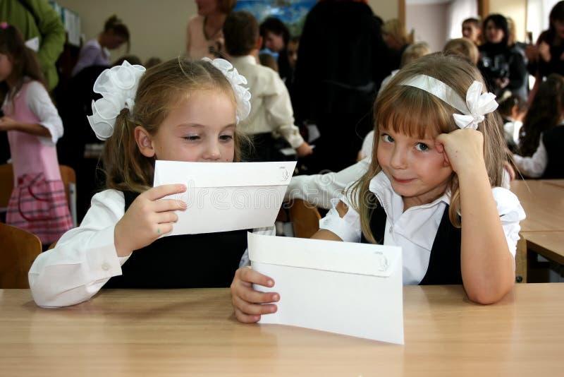 基辅,乌克兰, 24 10 2008两位小女小学生坐在书桌并且拿着白色信封 库存图片