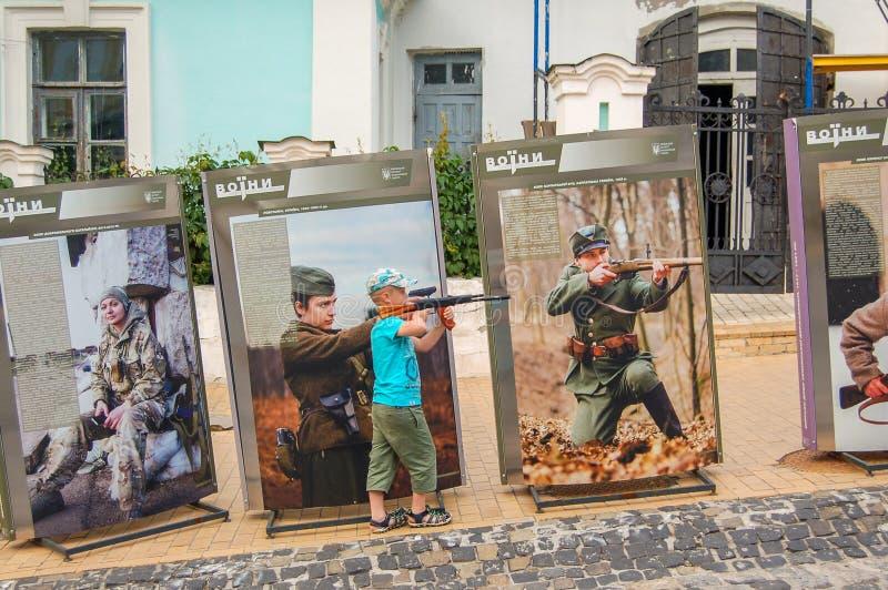 基辅,乌克兰,02-07-2017 安德鲁` s下降 有摆在广告牌背景的一杆假装步枪的一个小男孩  在广告牌 库存图片