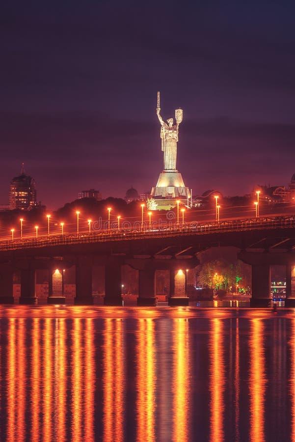 基辅,乌克兰- 2018年5月04日:佩顿桥梁、祖国纪念碑和第聂伯河的看法在晚上,美好的都市风景 免版税库存图片