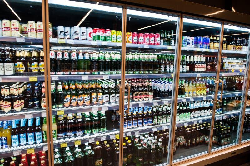 基辅,乌克兰- 2018年12月19日:在冰箱架子的不同的啤酒瓶在超级市场 免版税库存照片