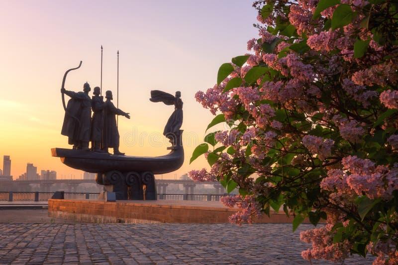 基辅,乌克兰- 2018年5月05日:对基辅基辅的创建者的纪念碑日出的,与丁香的美好的都市风景 图库摄影