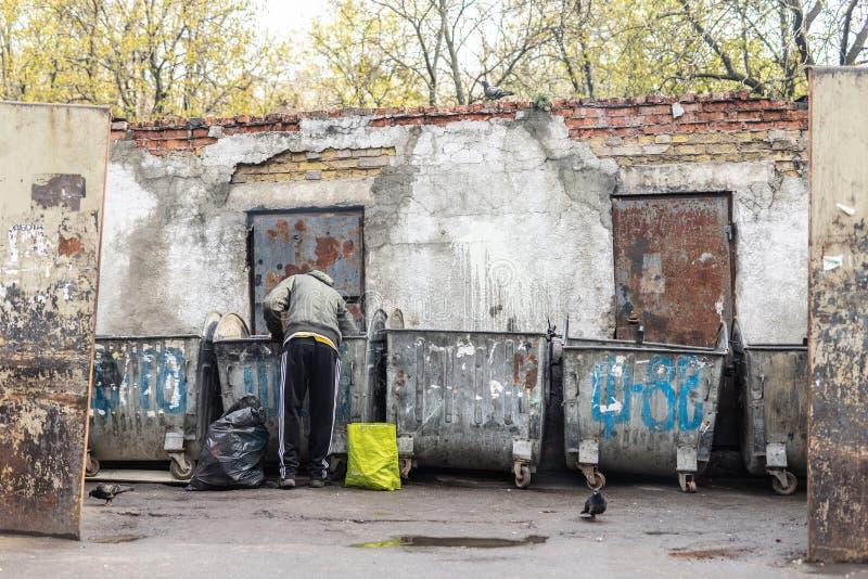 基辅,乌克兰- 2019年4月20日:搜寻在垃圾箱的食物的无家可归的叫化子在城市街道 Unemployement和贫穷 免版税库存照片