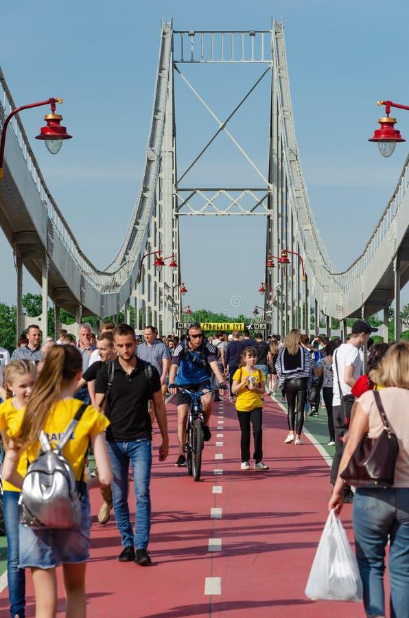 基辅,乌克兰- 2019年5月18日 在Dnipro河的公园桥梁 走沿步行桥的人们周末 图库摄影