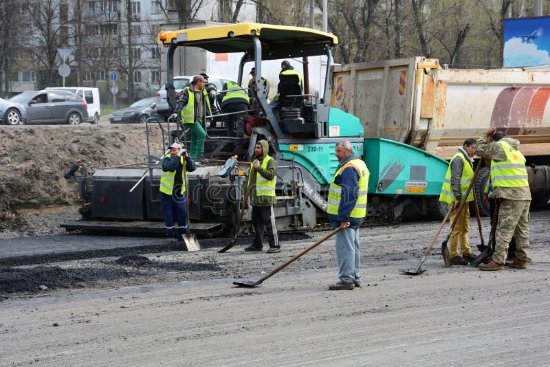 基辅,乌克兰- 2017年4月6日:操作沥青摊铺机机器和大量手段的工作者在路修理期间 免版税库存图片