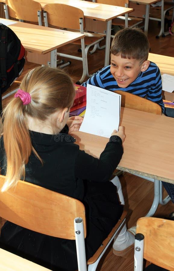 基辅 乌克兰,26 04 笑的男小学生从前台转动给坐在他后的女小学生在教室的2010 免版税库存图片