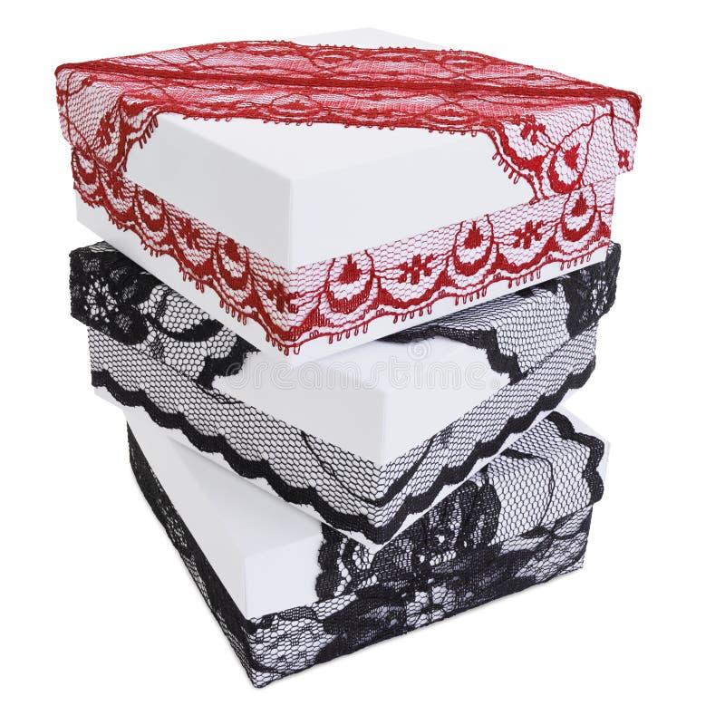 堆三个时髦的白色礼物盒,装饰用精妙的黑和红色鞋带丝带 库存照片