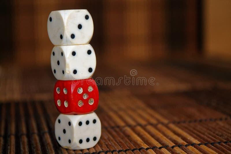 堆三白色塑料切成小方块和在棕色木板背景的一个红色模子 与黑小点的六个边立方体 第3, 4, 库存图片