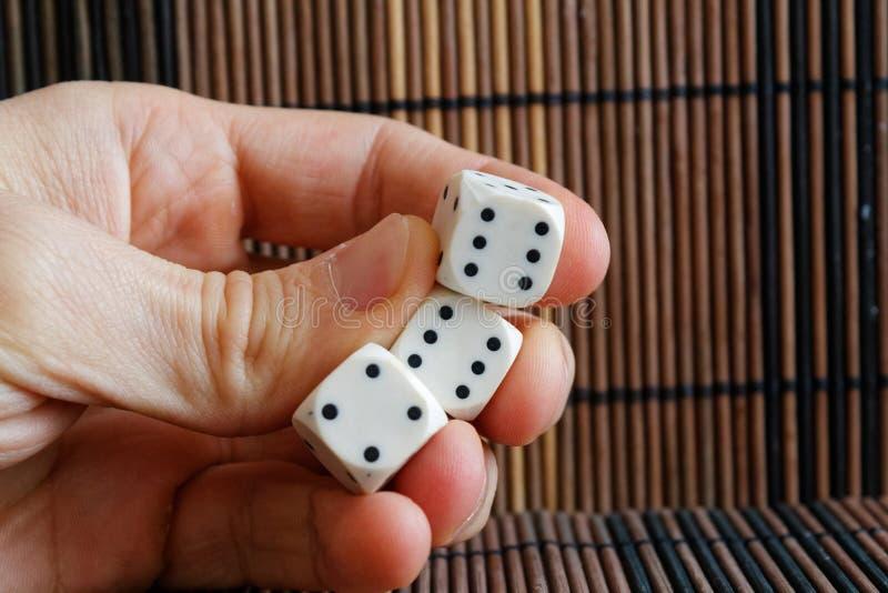 堆三白色塑料在人在棕色木桌背景的` s手上切成小方块 与黑小点的六个边立方体 第4, 6, 6 库存图片