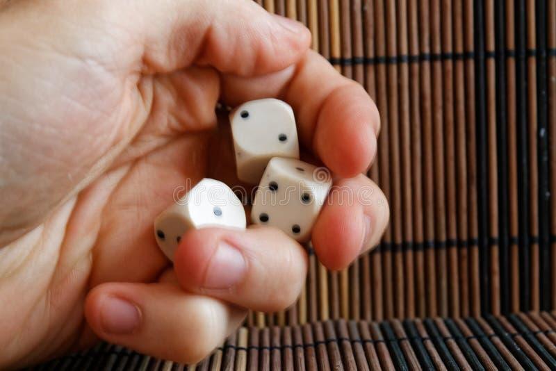 堆三白色塑料在人在棕色木桌背景的` s手上切成小方块 与黑小点的六个边立方体 第1, 4, 2 免版税库存照片