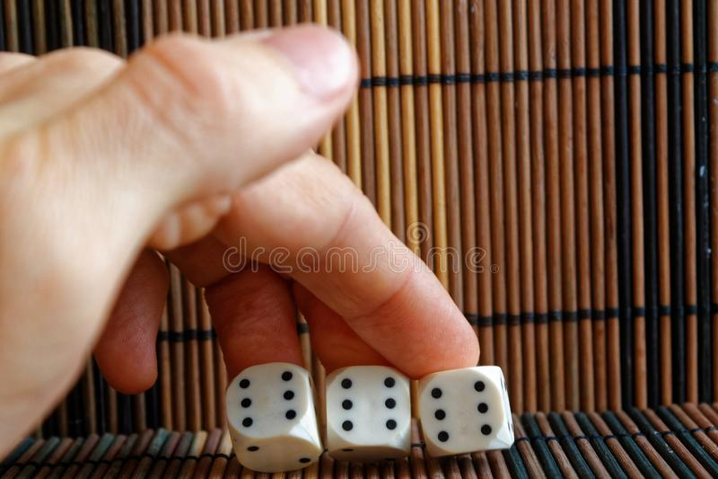 堆三白色塑料在人在棕色木桌背景的` s手上切成小方块 与黑小点的六个边立方体 第6, 6, 6 免版税库存图片