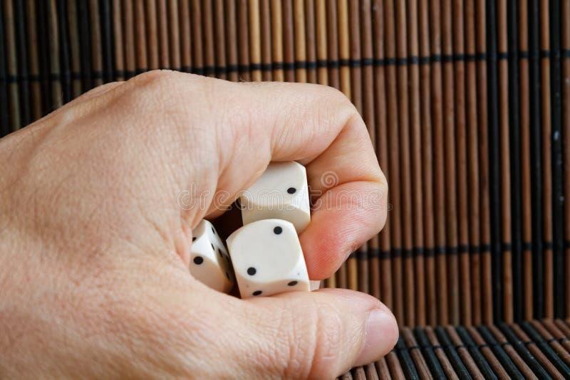堆三白色塑料在人在棕色木桌背景的` s手上切成小方块 与黑小点的六个边立方体 图库摄影