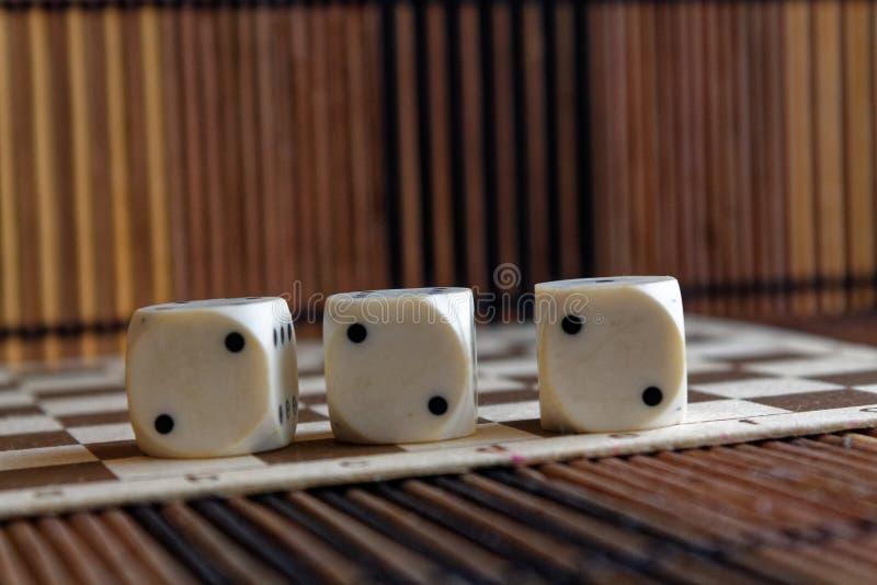 堆三白色塑料在棕色木板背景切成小方块 与黑小点的六个边立方体 第2 免版税图库摄影