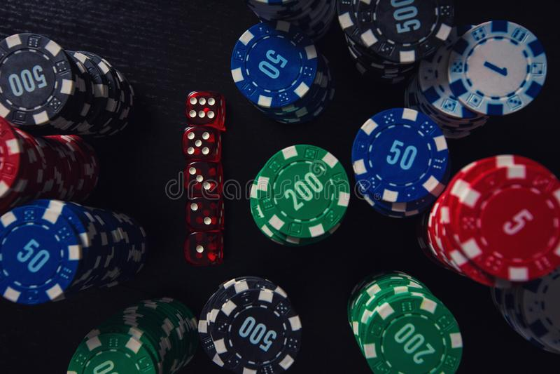 堆不同的色的纸牌筹码和使用在赌博娱乐场桌上切成小方块被隔绝在黑背景 赌博的比赛 库存图片