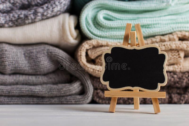 堆不同颜色和纹理被编织的衣裳,在桌上在一个地方旁边文本的 复制空间 免版税库存照片