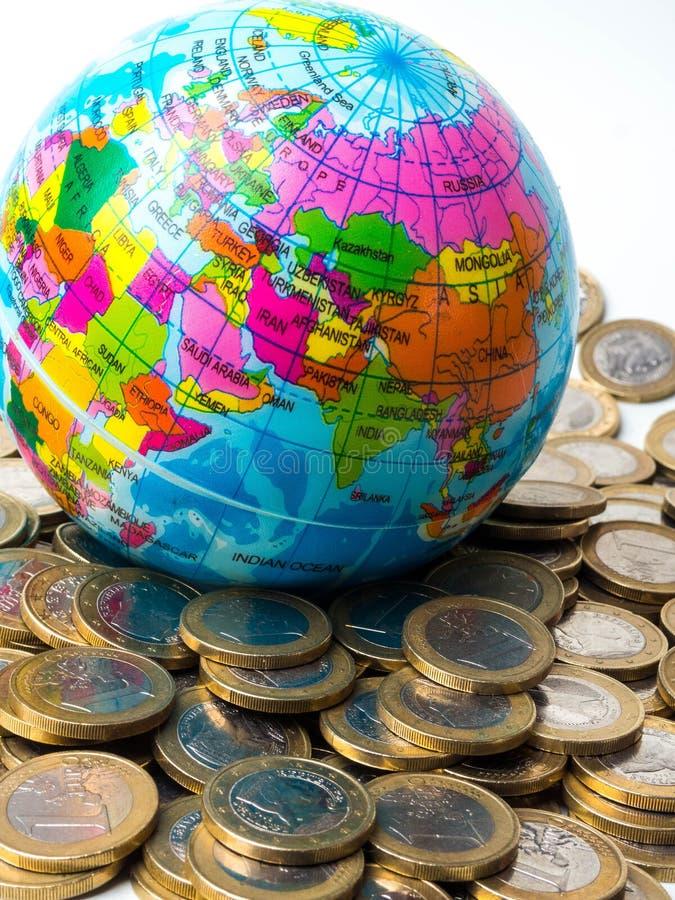 堆与世界行星在背景-保存行星的概念的硬币,关系的概念金钱之间的,经济 免版税库存图片