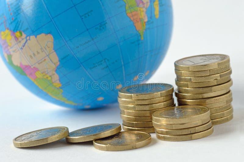 堆与世界行星在背景-保存行星的概念的硬币,关系的概念金钱之间的,经济 图库摄影