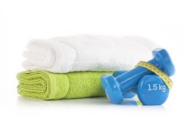 堆与两涂哑铃被包裹的蓝色乙烯基的白色和绿色毛巾用黄色测量的磁带 健康离开和fitnes 免版税库存图片