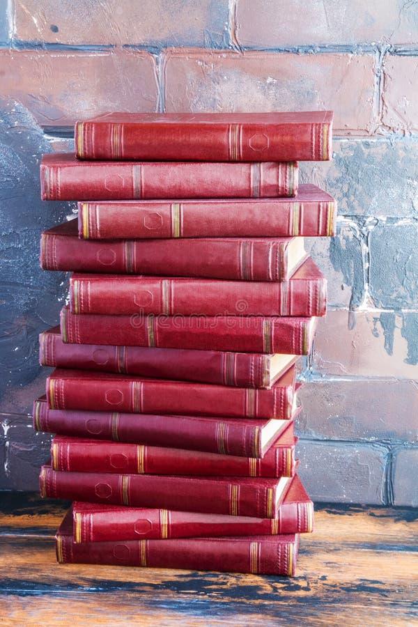 堆与后边深红坚硬盖子的书在以棕色砖墙为背景的一张木桌上 图库摄影