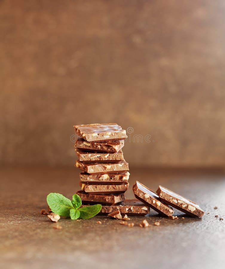 堆与坚果的牛奶巧克力酒吧装饰了棕色表面上的绿色薄荷叶 免版税库存图片