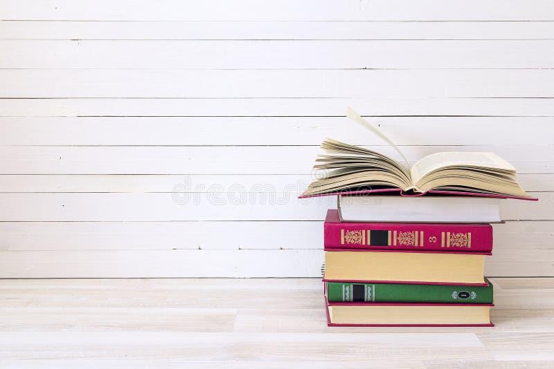 堆与开放书的书在木桌上 复制te的空间 免版税库存图片