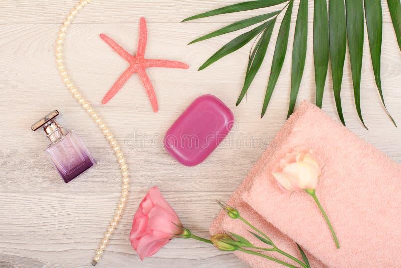 堆与桃红色花、肥皂、瓶香水,海星和绿色叶子的软的特里毛巾在木背景 免版税库存图片