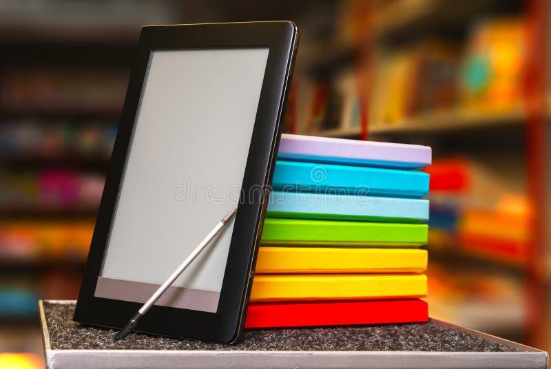 堆与电子书读者的五颜六色的书 免版税图库摄影