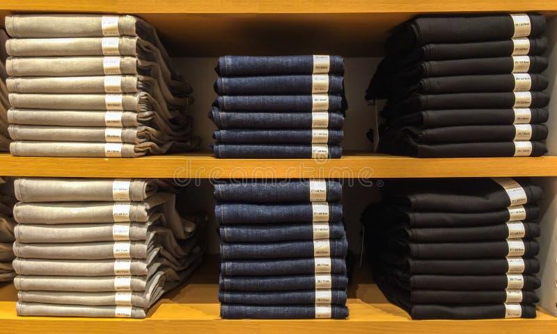 堆与纸标记展览的经典浅灰色,蓝色和黑牛仔裤纹理的混合大小在木架子 免版税库存图片