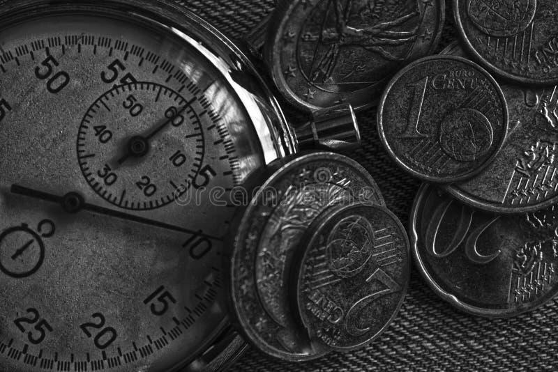 堆与老葡萄酒秒表的欧洲硬币在破旧的老牛仔裤背景 免版税库存图片