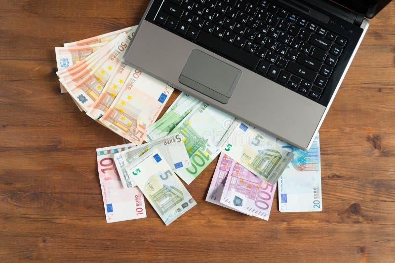 堆与膝上型计算机的欧洲金钱 库存图片