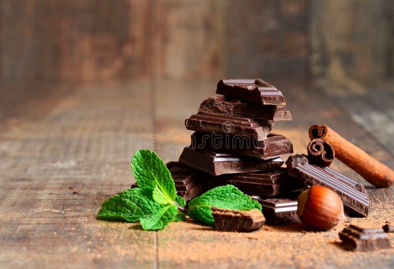 堆与薄荷的叶子、榛子和桂香的巧克力切片 免版税库存图片