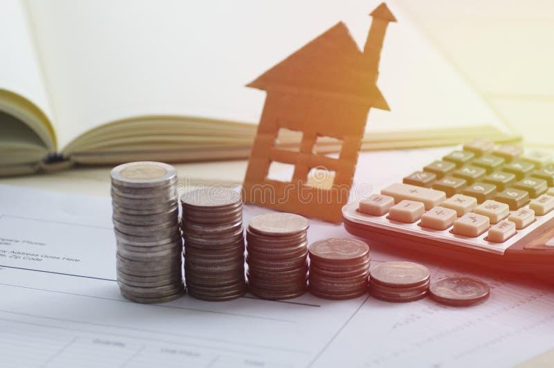 堆与计算器和房子的硬币 免版税库存图片