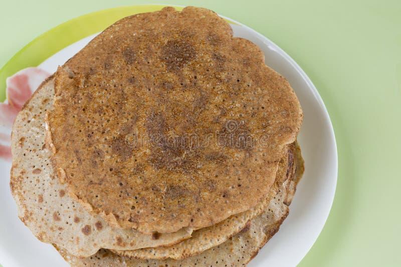 堆与酥脆外壳的稀薄的薄煎饼在板材 免版税库存照片