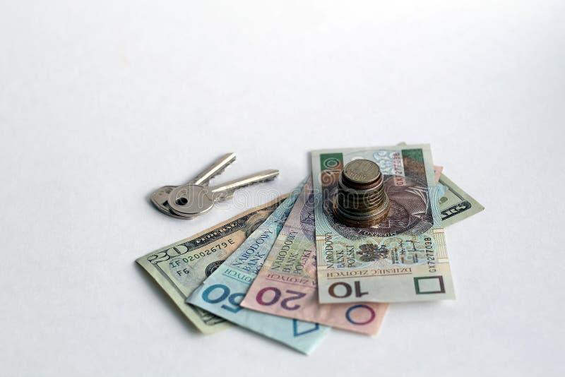堆与钞票和钥匙的硬币 免版税库存照片