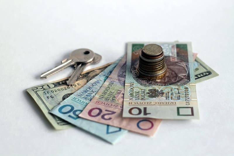 堆与钞票和钥匙的硬币 免版税库存图片