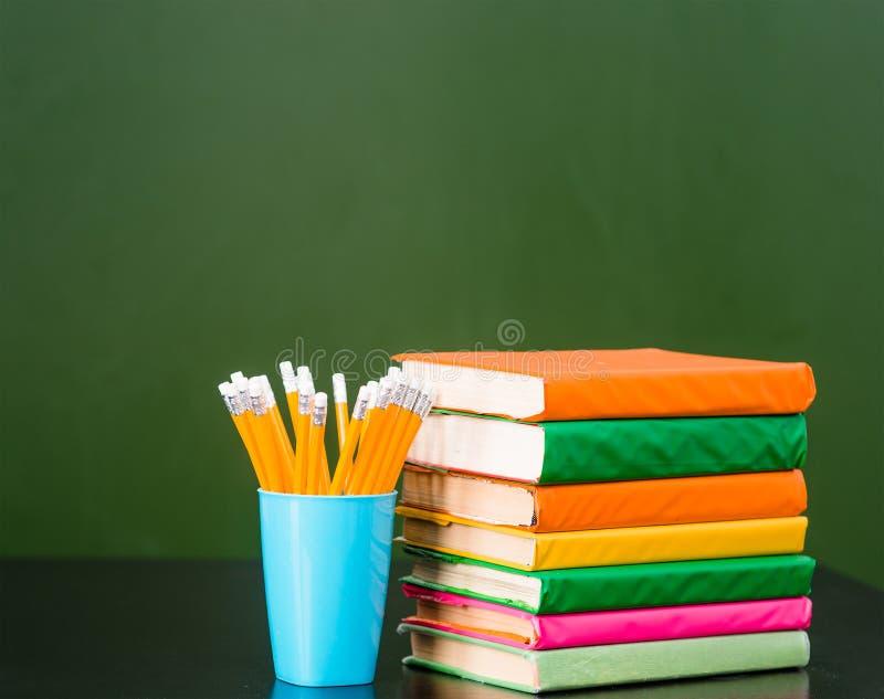 堆与铅笔的书临近空的绿色黑板 文本的样品 免版税库存图片